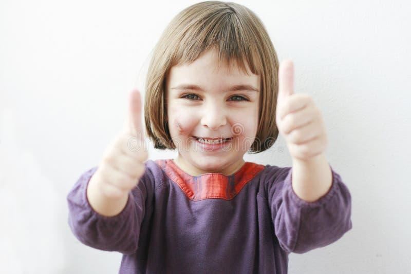 Meisje dat o.k. teken met beide handen toont stock foto