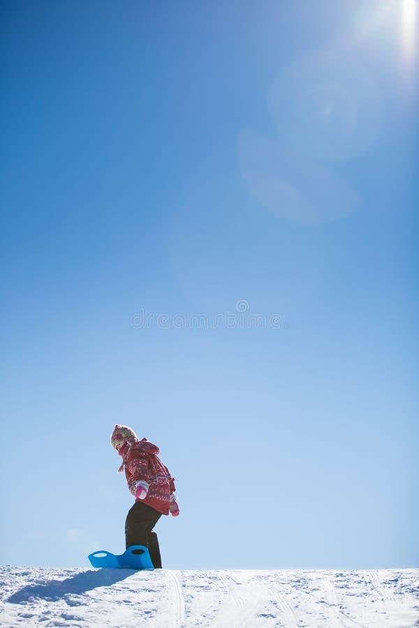Meisje dat onderaan een heuvel glijdt stock afbeeldingen