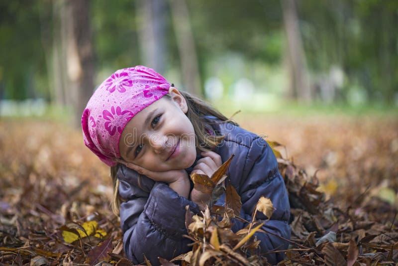 Meisje dat op de herfstbladeren legt stock foto's