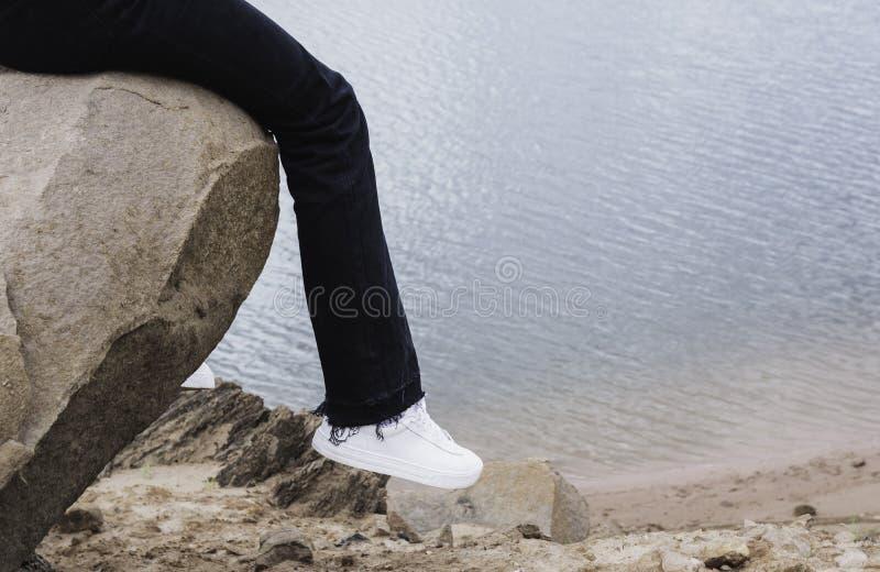 Meisje dat op een rots rust Vrouwenzitting op rots dichtbij rivier stock afbeeldingen