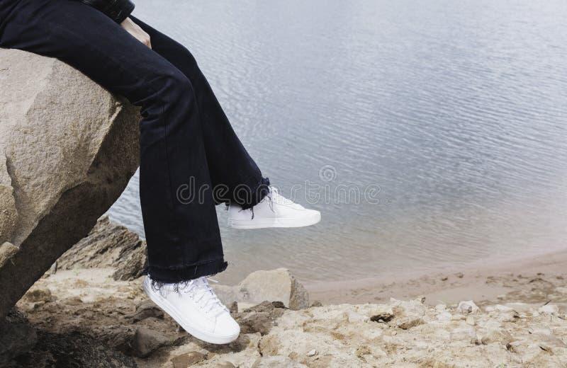 Meisje dat op een rots rust Vrouwenzitting op rots dichtbij rivier stock foto
