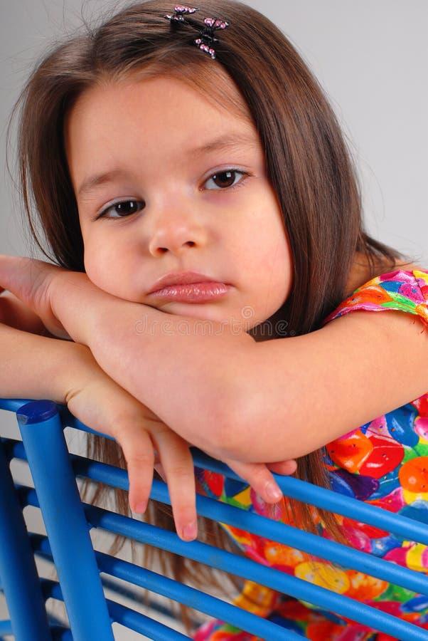 Meisje dat op een stoel rust stock foto