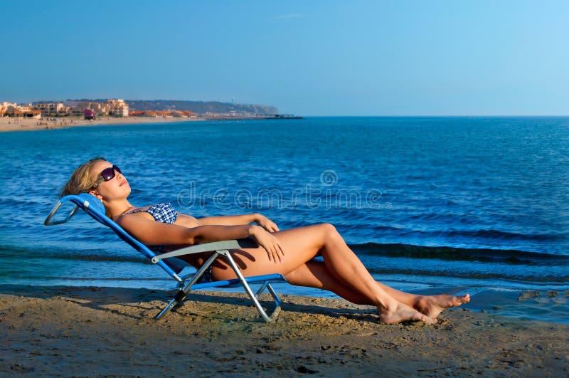 Meisje dat op een strand ligt stock foto