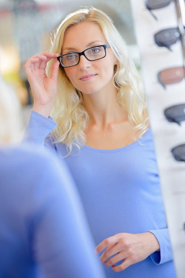 Meisje dat op glazen met zwarte randen probeert royalty-vrije stock foto's