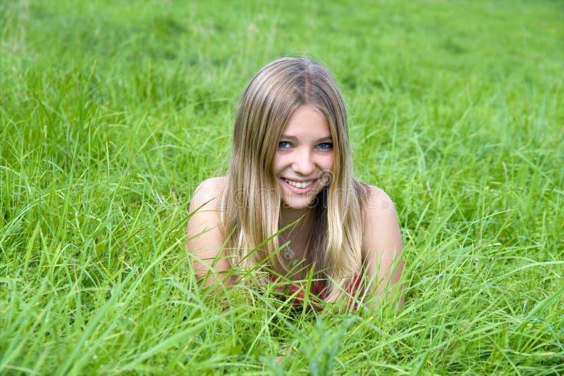 Meisje dat op grasgebied ligt stock afbeelding