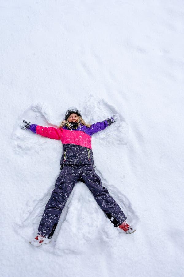 Meisje dat op sneeuw legt en engel maakt stock foto