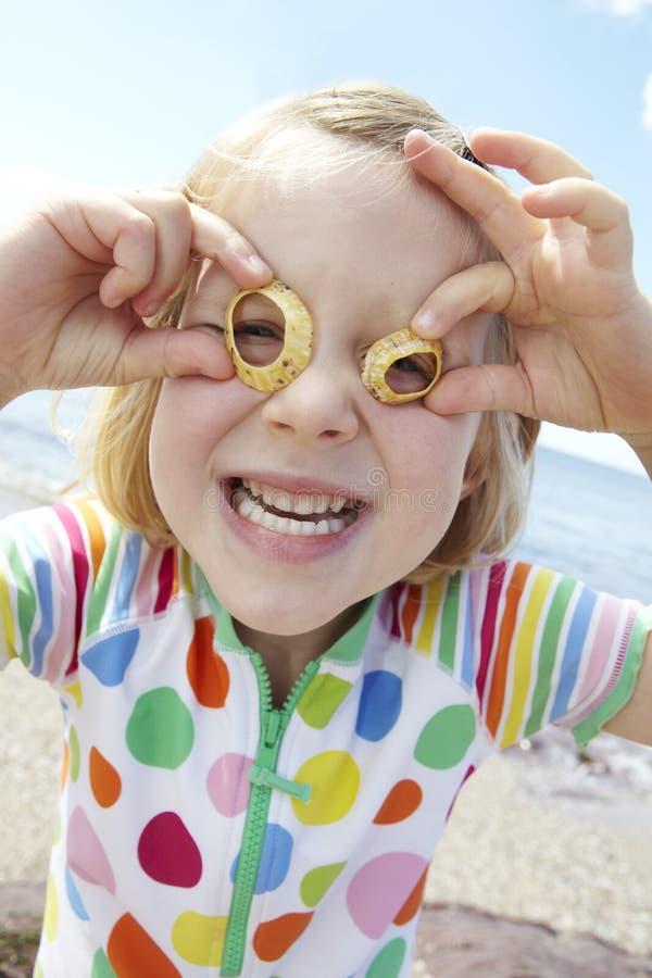 Meisje dat op Strand Glazen van Zeeschelpen maakt stock fotografie
