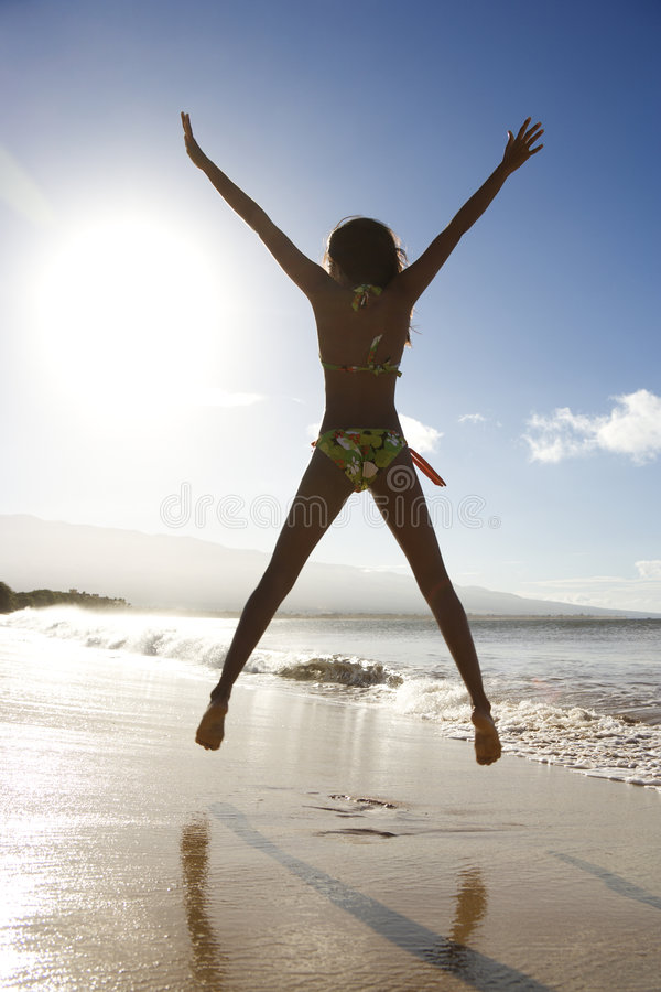 Meisje dat op strand springt. stock afbeeldingen