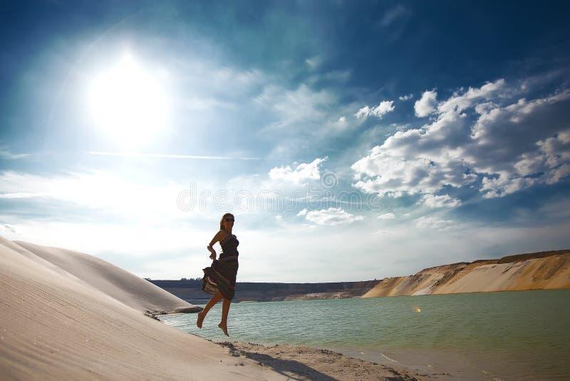 Meisje dat op strand springt stock foto