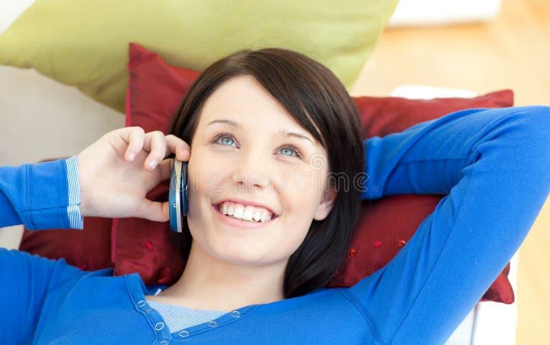 Meisje dat op telefoon spreekt die op een bank ligt stock foto's