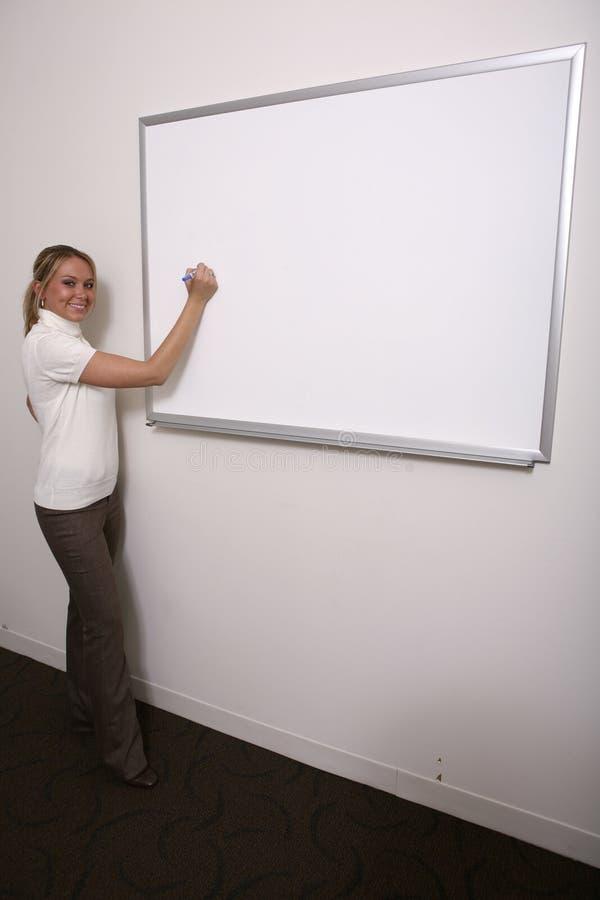 Meisje dat op volledige whiteboard schrijft stock afbeeldingen