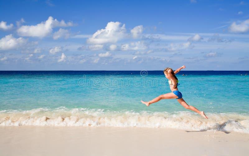 Meisje dat over baech en de golven springt royalty-vrije stock afbeeldingen