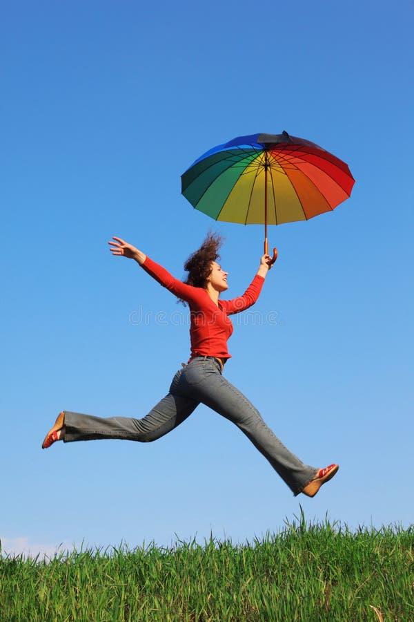 Meisje dat over gras met kleurrijke paraplu springt royalty-vrije stock foto's