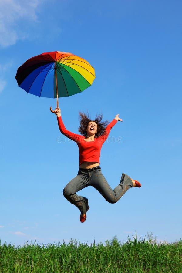 Meisje dat over groen gras met paraplu springt stock foto's