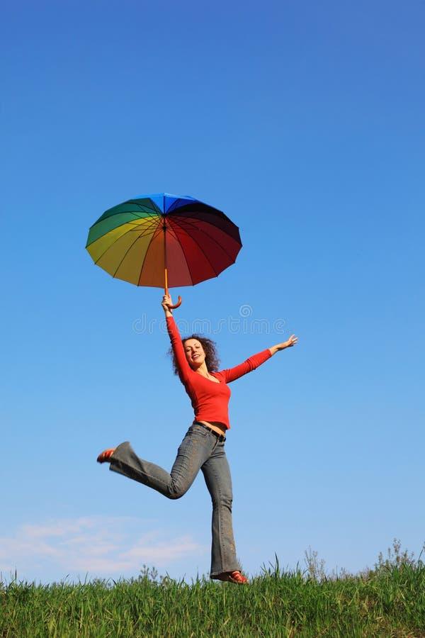 Meisje dat over groen gras met paraplu springt royalty-vrije stock fotografie