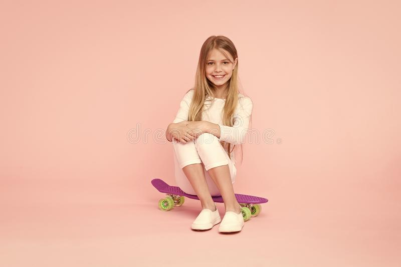Meisje dat plezier heeft met een roze achtergrond op een penny board Kid adorable child long hair adore ride penny board Ride pen royalty-vrije stock fotografie