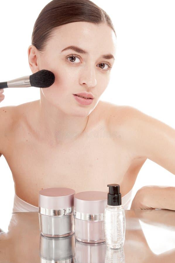 Meisje dat poeder toepast door borstel op haar gezicht. stock afbeeldingen