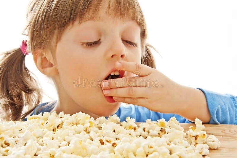 Meisje dat popcorn eet stock foto