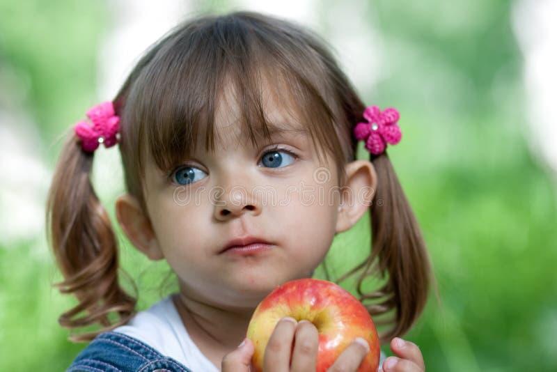 Meisje dat rode appel eet openlucht royalty-vrije stock fotografie