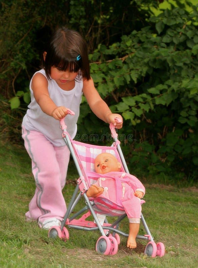 Meisje dat in Roze een Dolly in een Kinderwagen duwt. royalty-vrije stock foto
