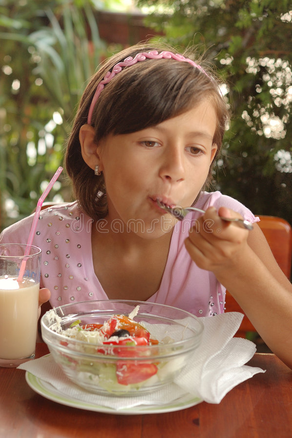 Meisje dat salade eet stock foto