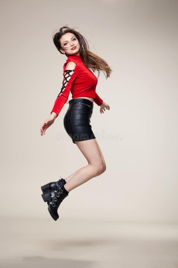 Meisje dat in studio springt stock foto's