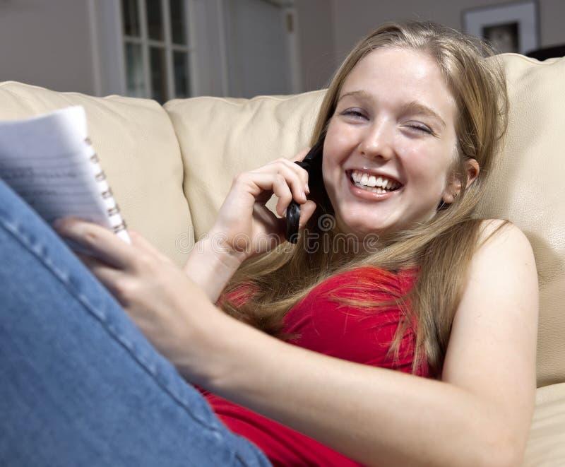 Meisje dat terwijl het Babbelen op de Telefoon van de Cel bestudeert royalty-vrije stock foto's