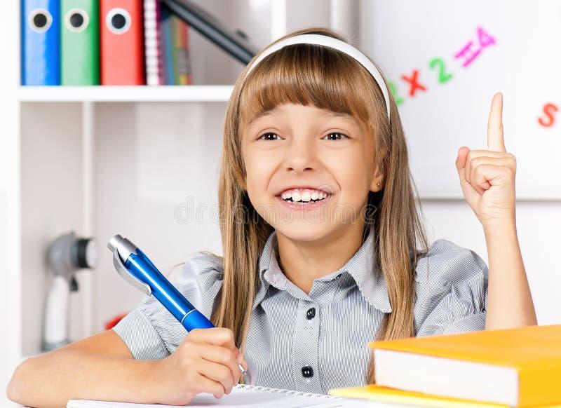 Meisje dat thuiswerk doet stock foto