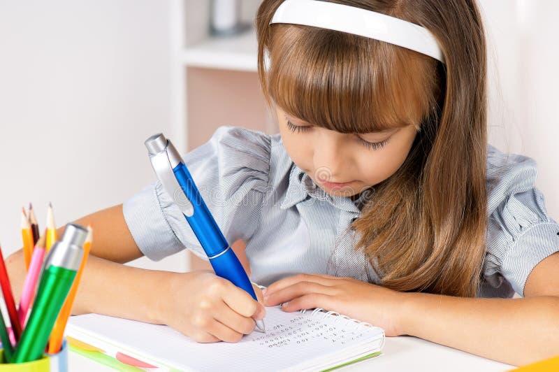 Meisje dat thuiswerk doet stock afbeelding