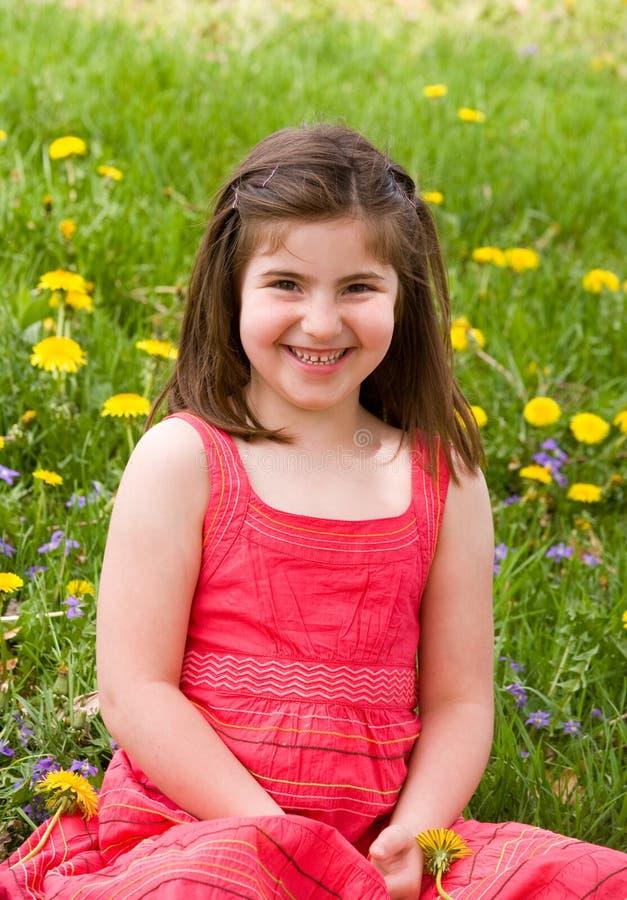 Meisje dat voor Bloemen glimlacht stock afbeelding