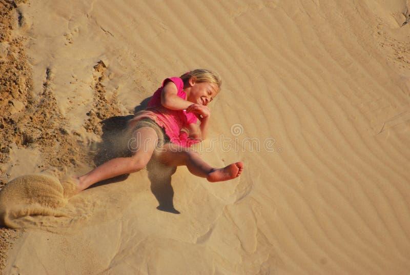 Meisje dat zandduin naar beneden rolt stock foto