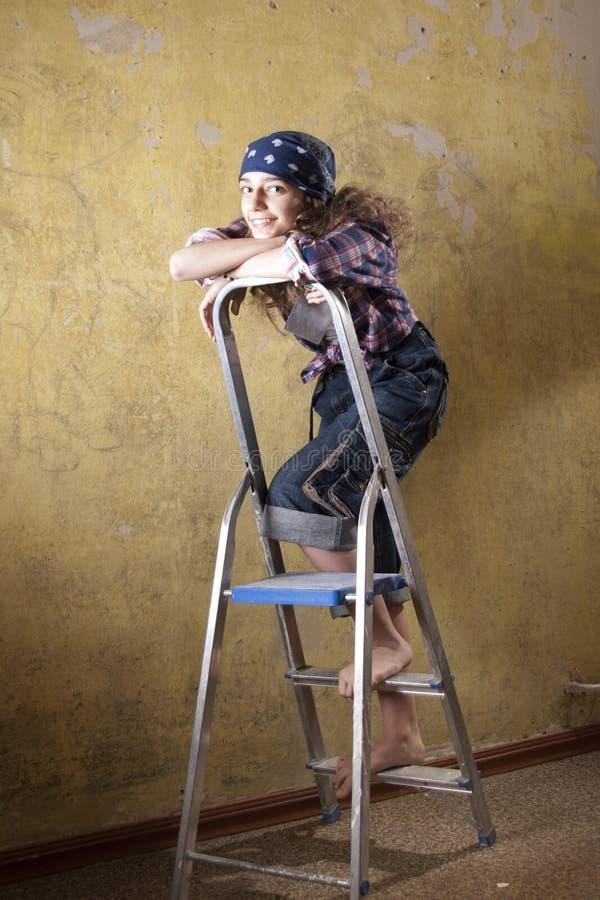 Meisje dat zich op de ladder bevindt stock afbeelding