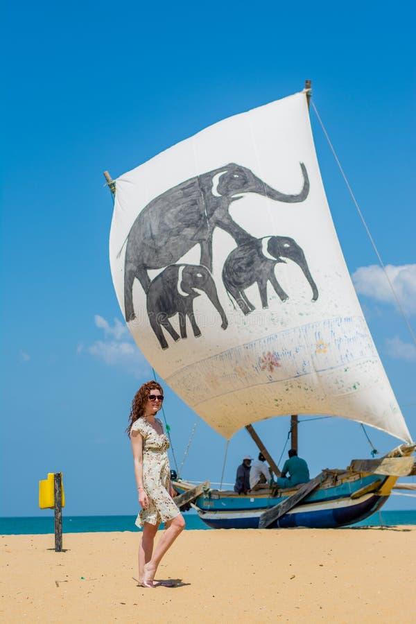Meisje dat zich op het strand bevindt dat dichtbij boot vaart stock foto's