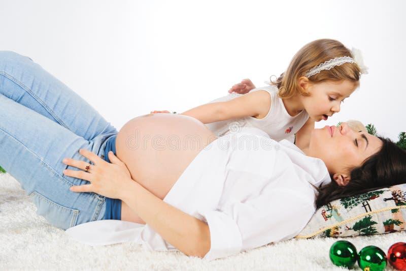 Meisje dat zwangere moeder kust stock foto's