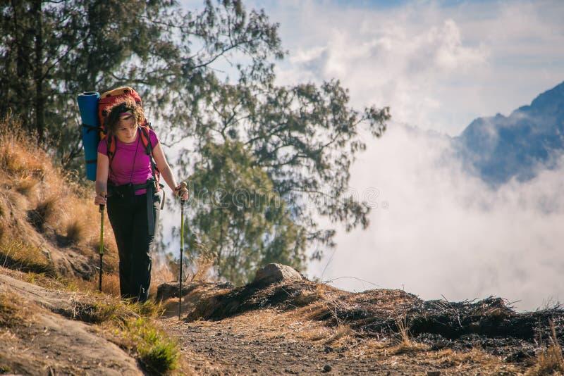 Meisje in de bergen met een zware rugzak stock afbeelding