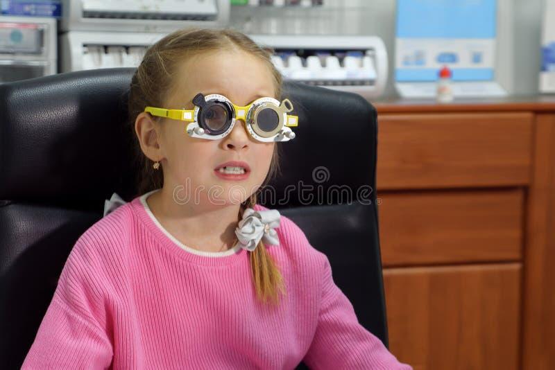 Meisje in de glazen van een oogtest in kliniek stock foto's