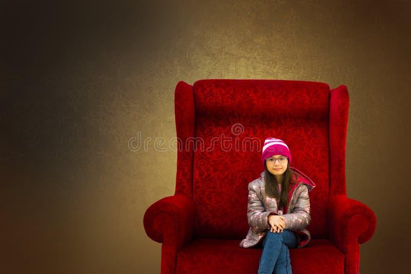 Meisje in de grote rode leunstoel stock afbeelding