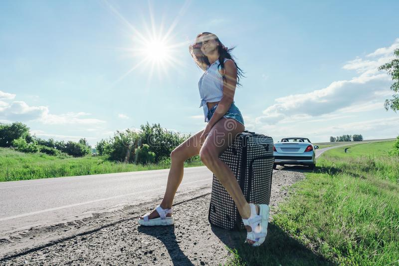 Meisje in de heldere zon op weg met Bagage op de achtergrond van de auto Kaukasische vrouwenzitting op een koffer E stock afbeeldingen