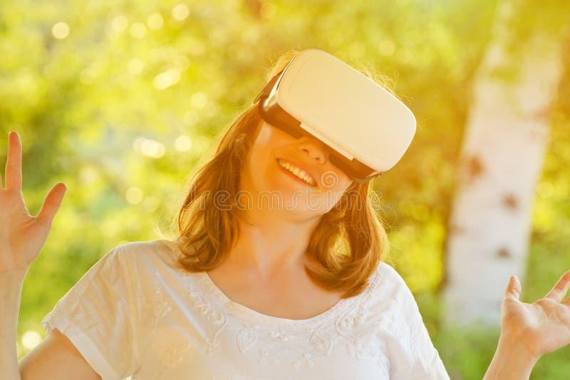 Meisje in de helm van virtuele werkelijkheid tegen de achtergrond van aard toning royalty-vrije stock foto