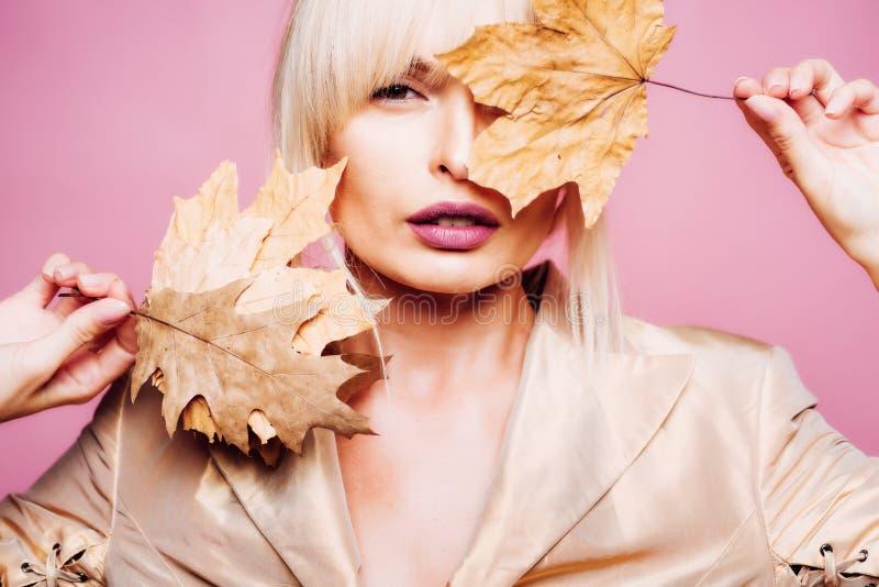 Meisje in de herfst het spelen met bladeren op de achtergrond van de herfstbladeren De mooie sexy jonge vrouw ligt op houten acht royalty-vrije stock foto