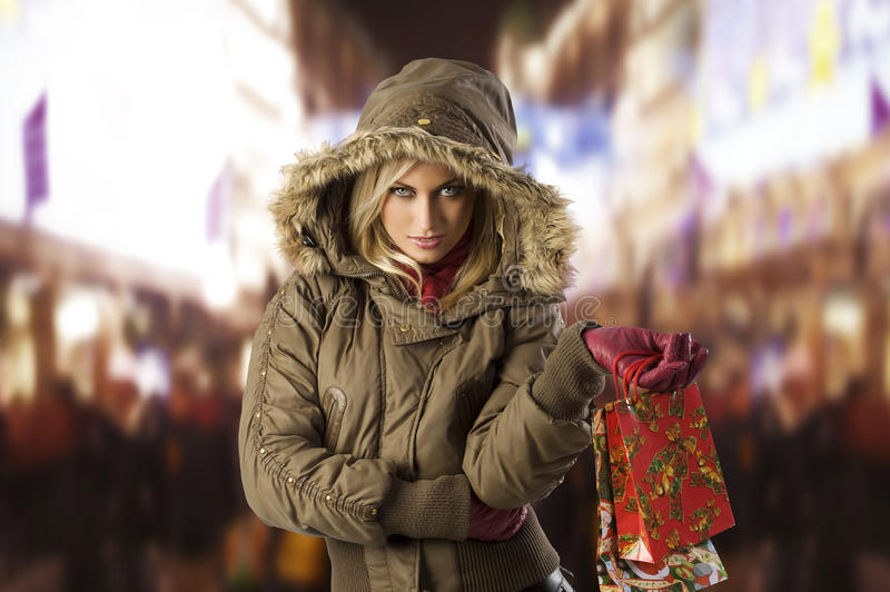 Meisje in de jasjewinter met het winkelen zak stock afbeelding