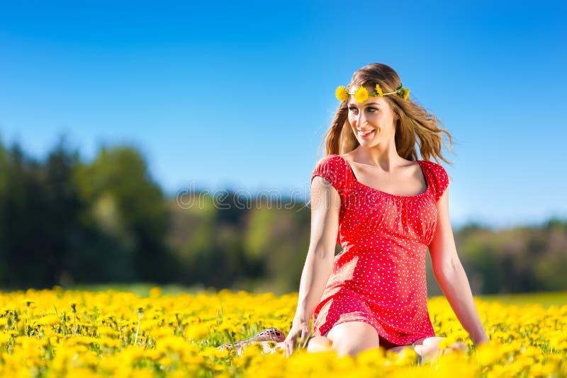 Meisje in de lente op een bloemweide met paardebloem stock afbeelding