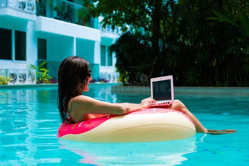 Meisje in de opblaasbare cirkel in de pool met laptop, het concept het freelancing en recreatie stock afbeelding