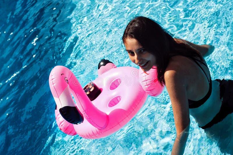 Meisje in de pool met een flamingovlotter royalty-vrije stock foto