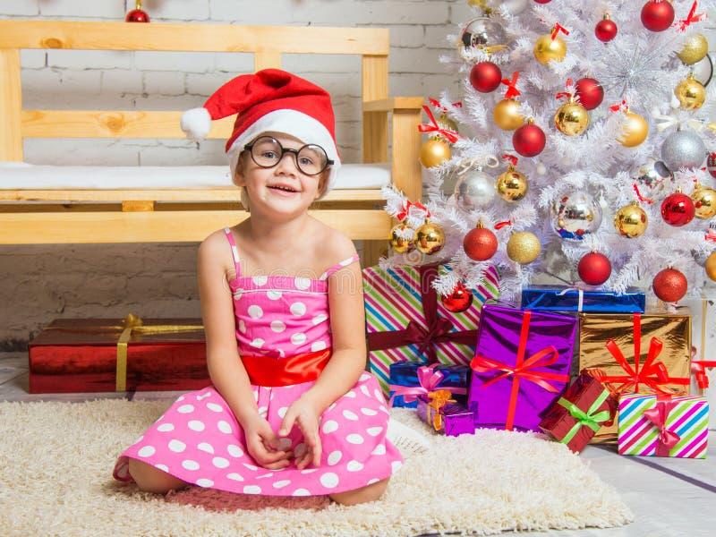 Meisje in de rode hoed en de grappige ronde glazen op een deken in Kerstmis het plaatsen royalty-vrije stock afbeeldingen