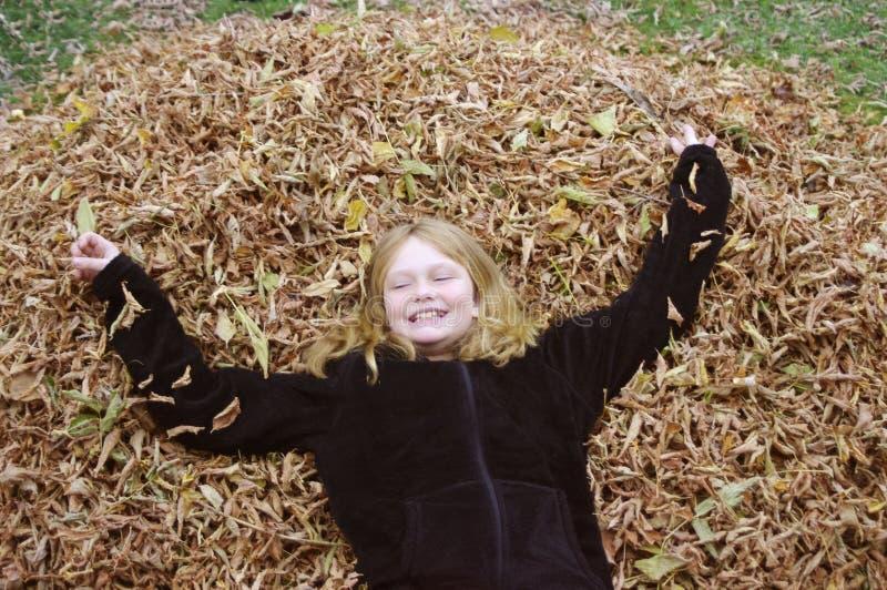 Meisje in de stapel van het dalingsverlof stock afbeeldingen