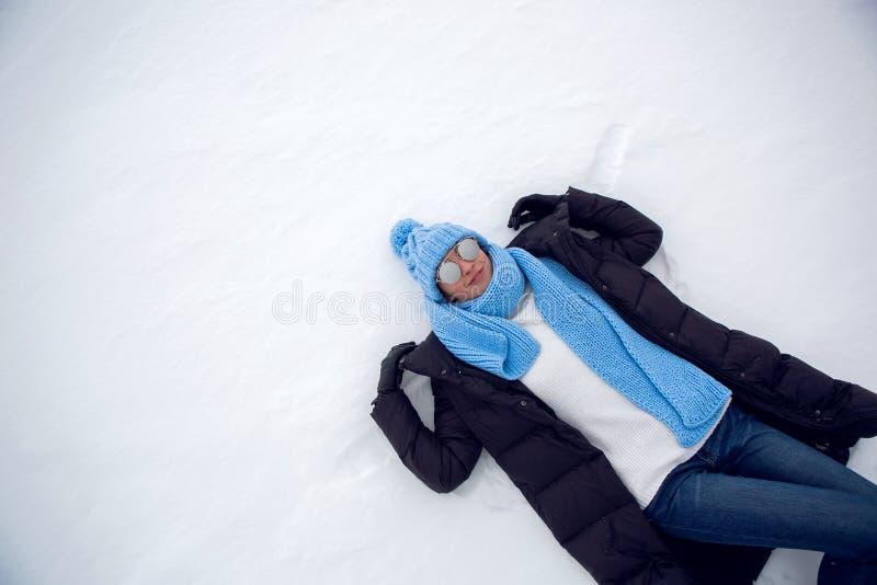 Meisje in de winterkleren het liggen stock foto's