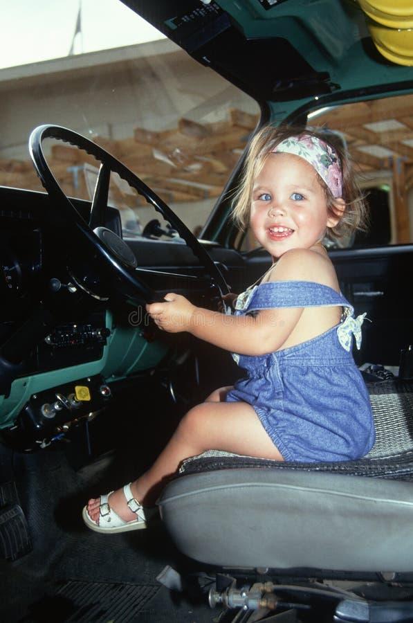 Meisje in de zetel van de bestuurder van grote installatievrachtwagen stock afbeeldingen