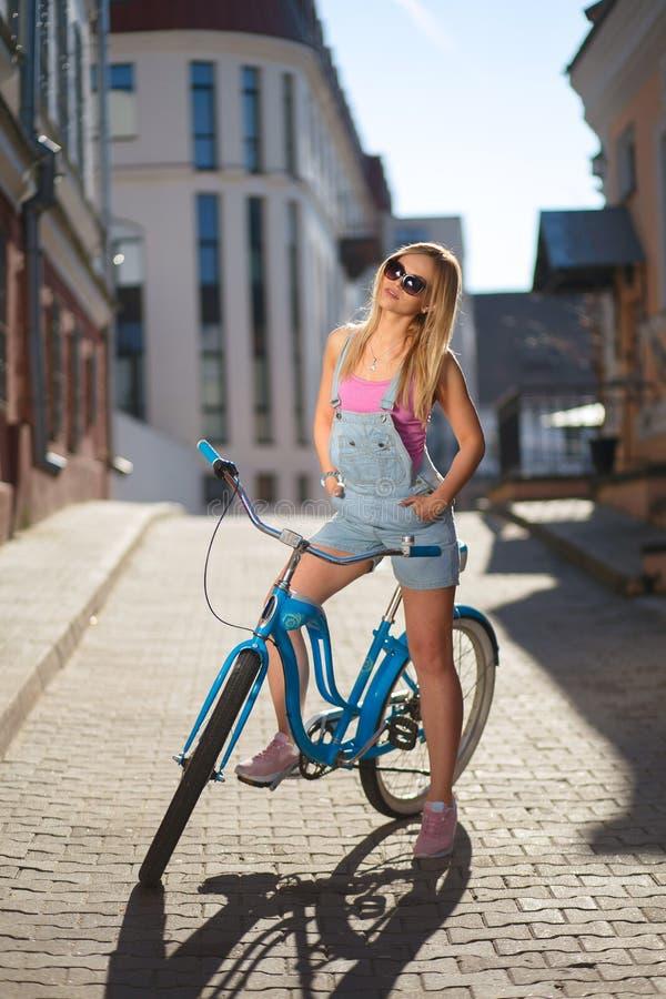 Meisje in de zon op een retro fiets stock fotografie
