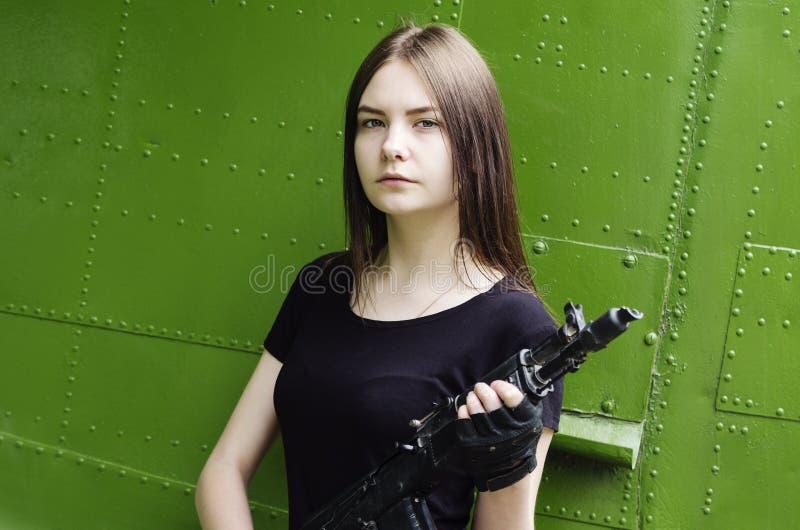 Meisje in de zwarte T-shirt met een kanon, die tegen de achtergrond van de vliegtuigen van het fuselage militaire vervoer stellen stock afbeelding